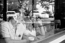a couple sitting in the window of a coffee shop