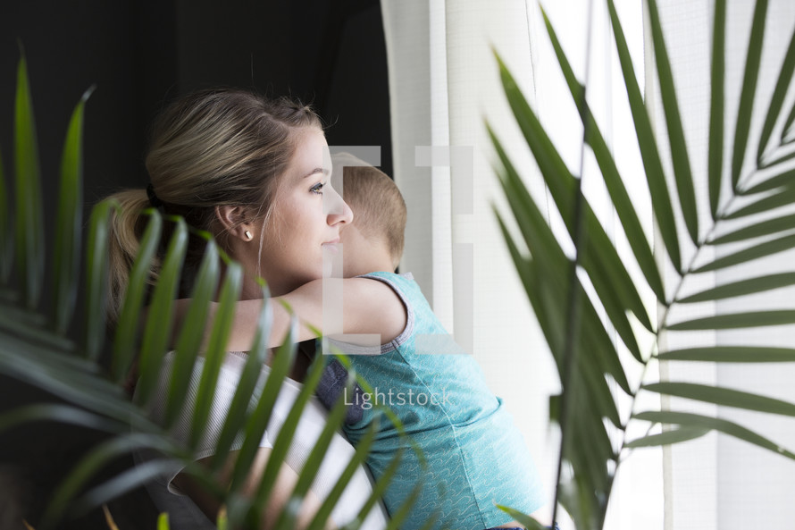a mother and son standing in a window looking out