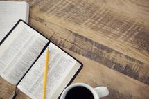 pencil on an open Bible and coffee mug