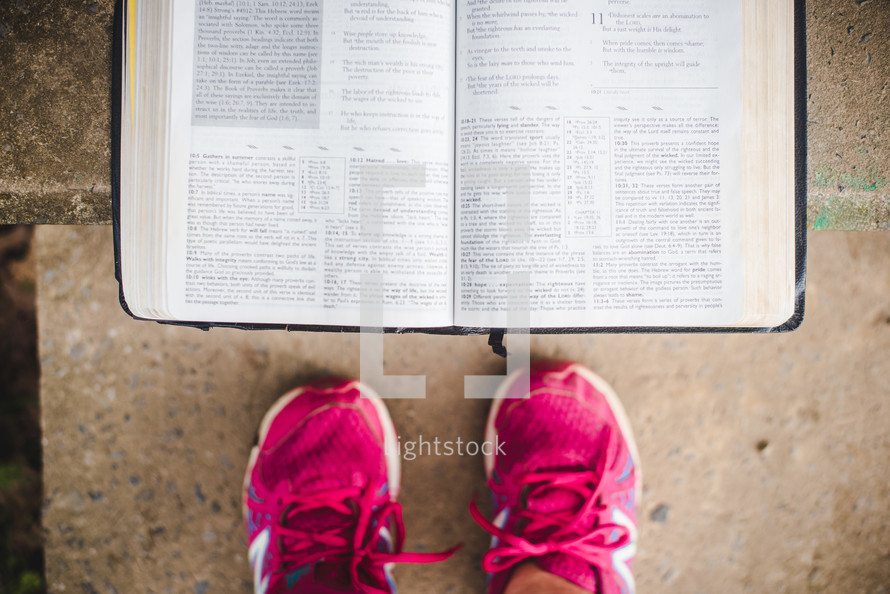 pink sneakers and open Bible on concrete