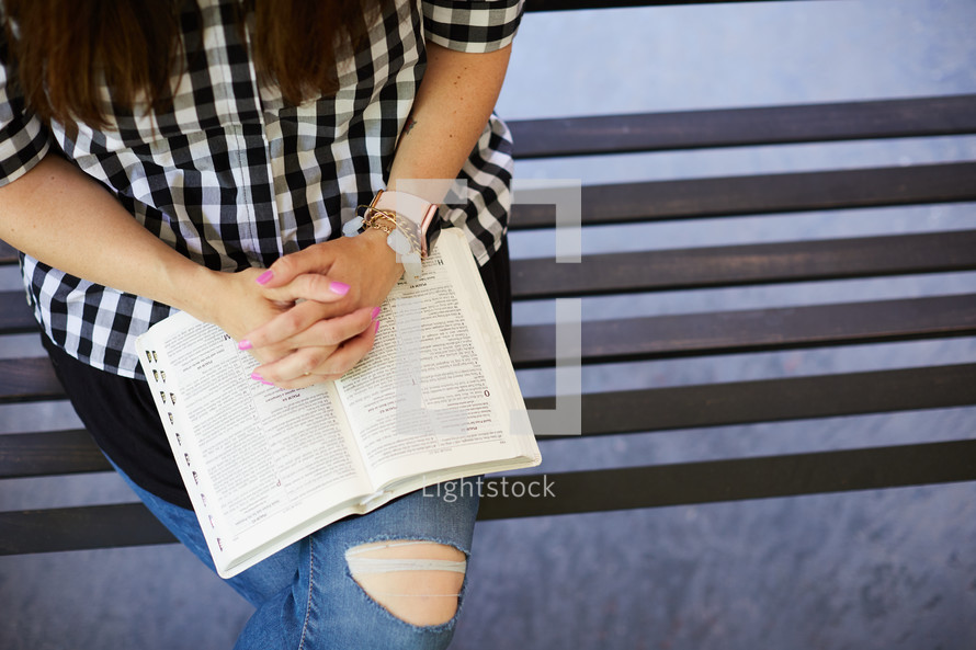 a woman sitting on a porch swing reading a Bible and praying