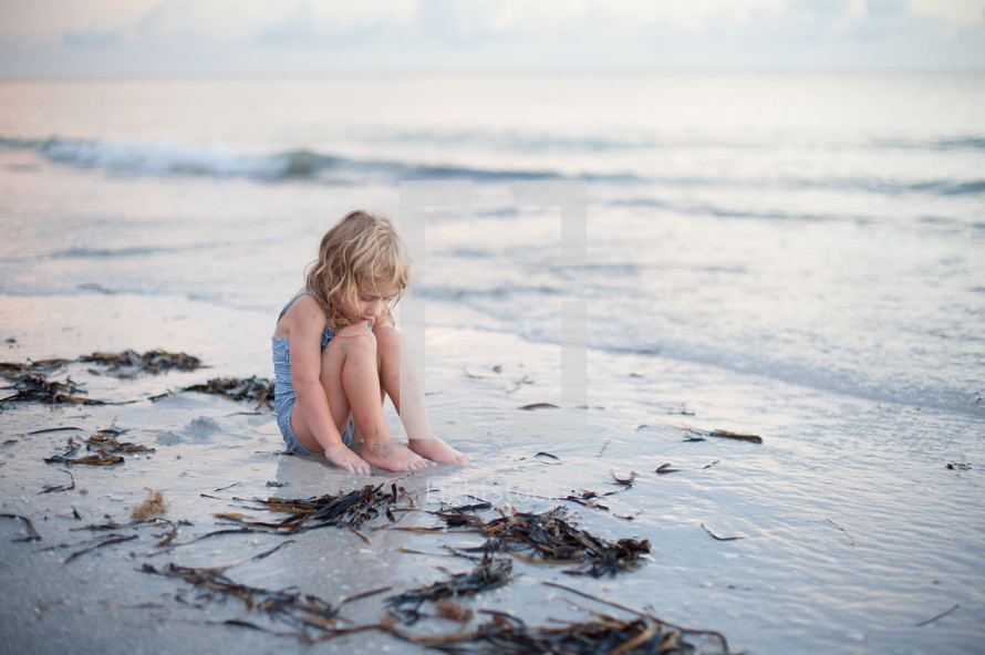 girl child in a bathing suit sitting in sand on a beach