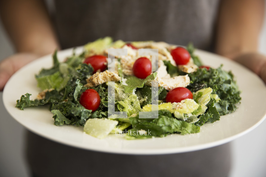 a woman holding a salad bowl