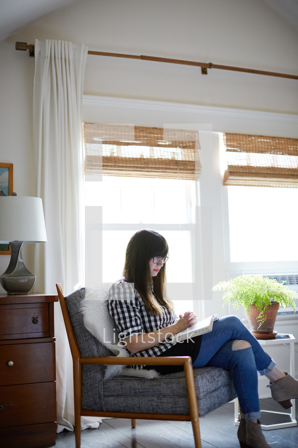 a woman sitting in an arm chair reading a Bible