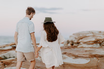 a couple walking on a rocky beach holding hands