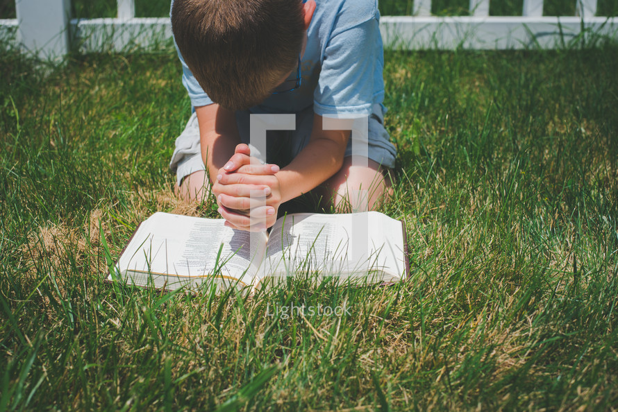 a boy kneeling in the grass reading a Bible and praying