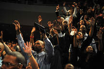 Congregation with arms raised praising God during worship service.