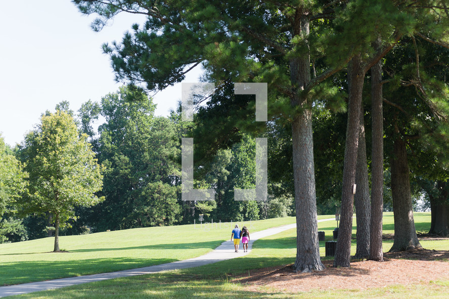 couple walking on a path in a park in summer