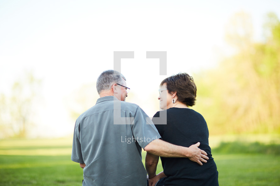 a older couple sitting outdoors snuggling