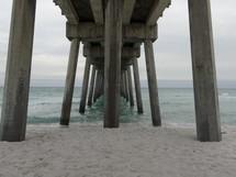 sand under a pier on a beach