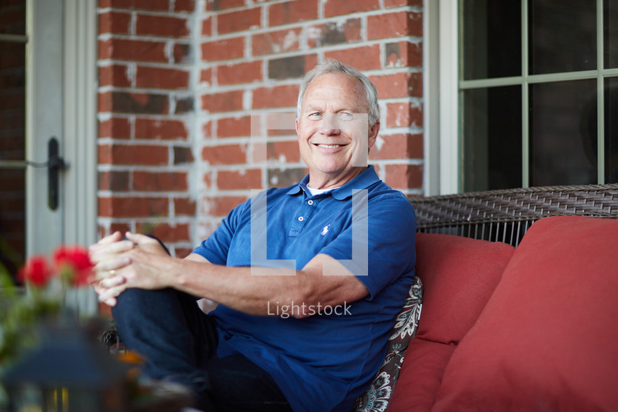 a smiling retiree sitting on a porch relaxing
