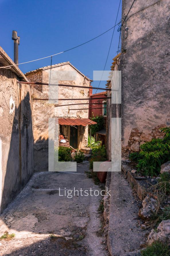broken concrete in a narrow alley between houses