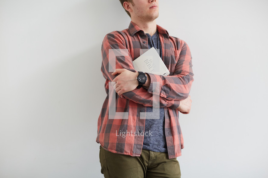 a man standing holding a Bible against his chest