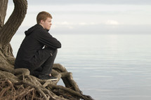 a man sitting on tree roots looking out at the ocean