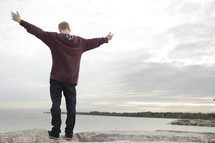 a man standing on a shore with outstretched arms