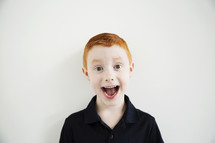 A red haired boy with his mouth wide open.