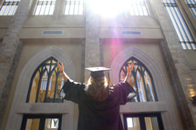 girl in cap and gown with her hands raised in worship to God
