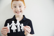 A smiling boy holding a paper cut-out of a family.