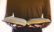 man standing holding a Bible