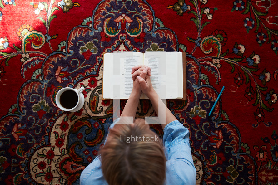 a woman praying over a Bible sitting on a rug