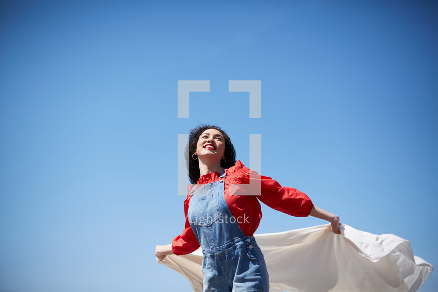 a woman with outstretched arms holding a white sheet and looking up