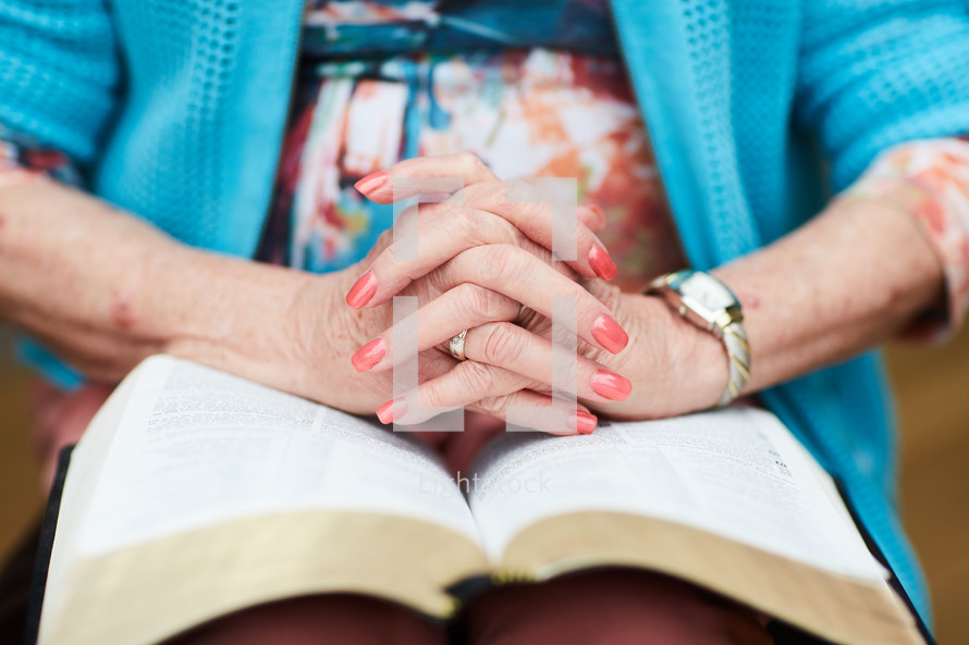 elderly woman with praying hands over a Bible