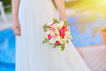 Bride in wedding dress holds her rouses bouquet