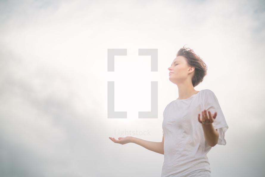 Woman standing outside praying.