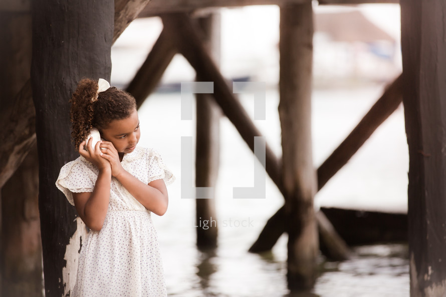 a girl listening to a seashell