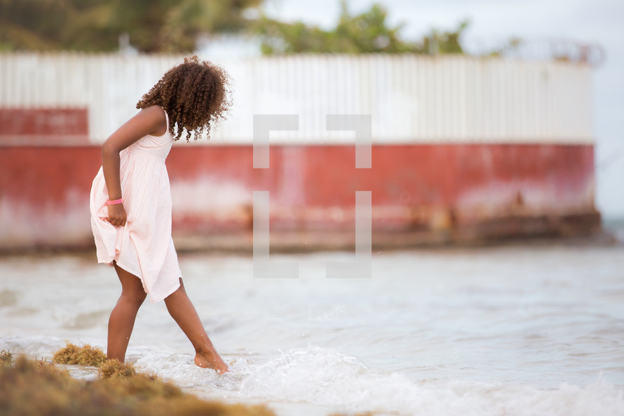 a child tipping her toes in the water
