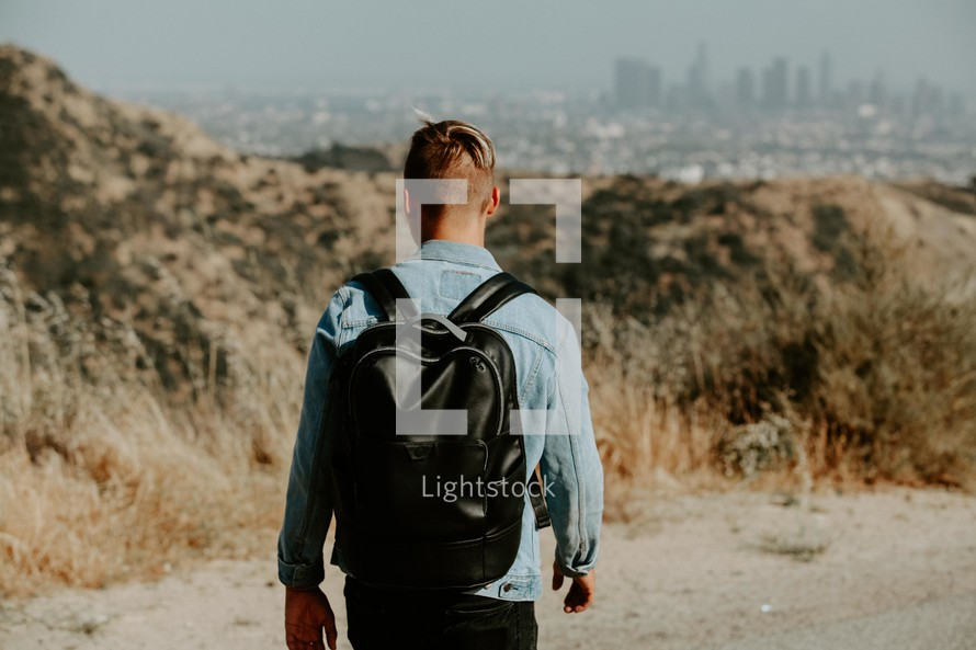 young man with a backpack and distant city