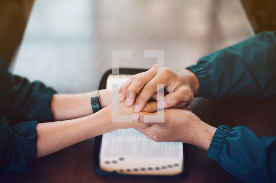 a couple holding hands over an open Bible