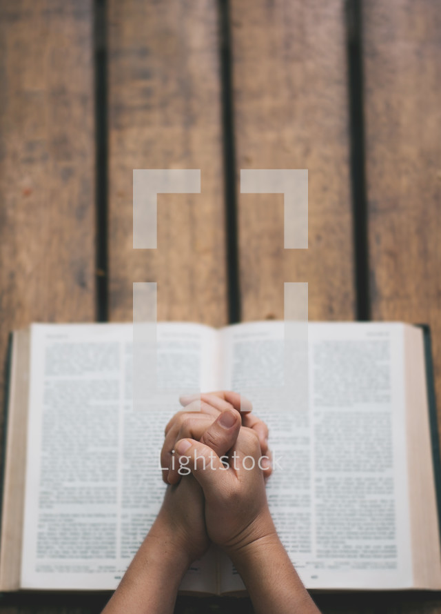 praying hands over the pages of an open Bible