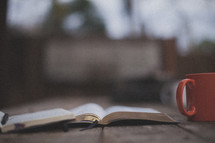 An open Bible and notebook next to an orange coffee mug