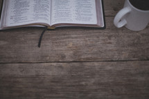 An open Bible and coffee mug on wood