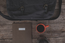 A bag, notebook, coffee mug and french press on wood