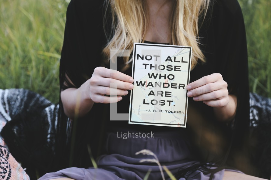 "Woman's hands holding a sign which reads ""Not all those who wander are lost."" -- A J.R.R. Tolkien quote."