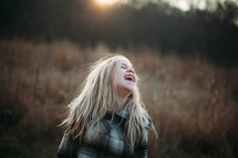 a girl laughing in a field