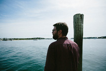 a man standing on a dock looking out at the harbor