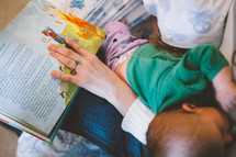 Mother reading a book to her infant child.