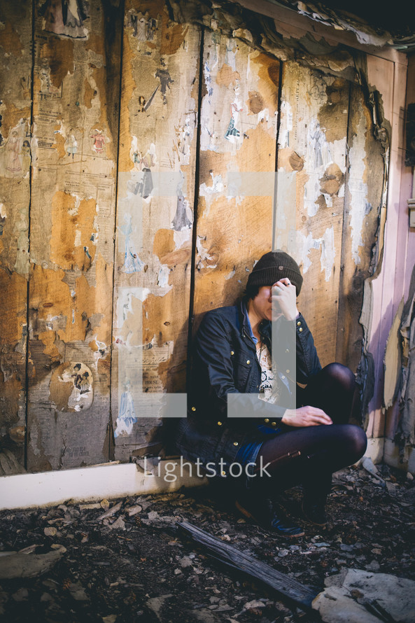 A woman sits in an abandoned house with her hand over her face.