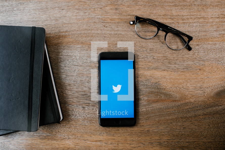 Bible, journal, cellphone with twitter app, and reading glasses on a wood table