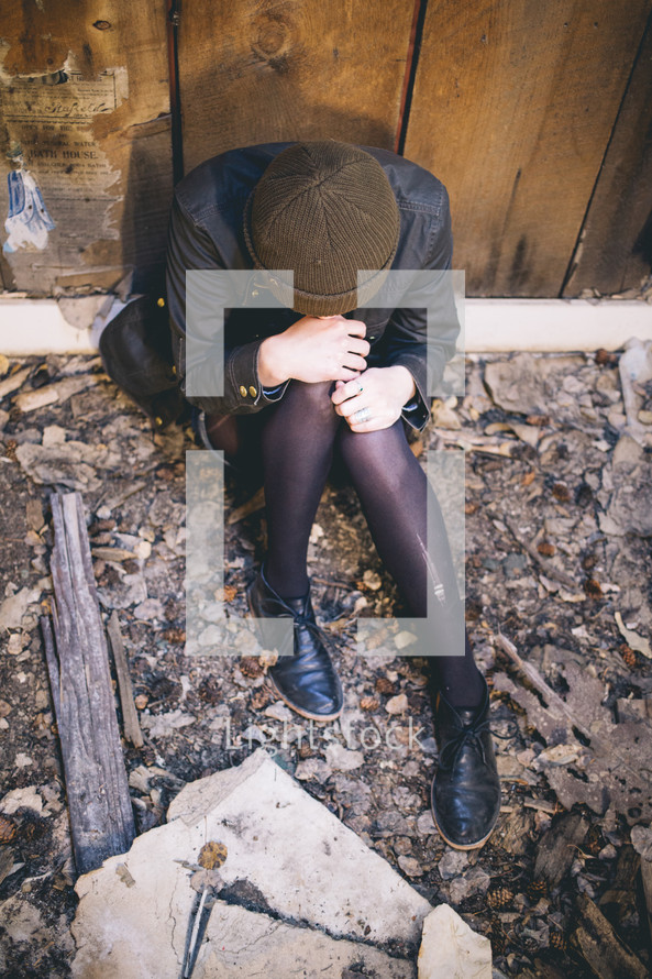 A woman sits with head bowed in an abandoned house.