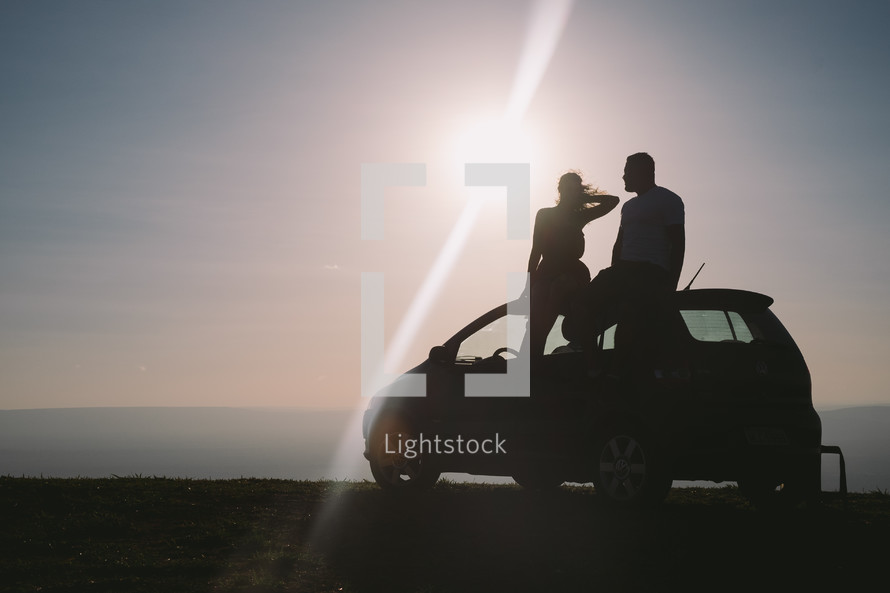 silhouette of a couple sitting on a car