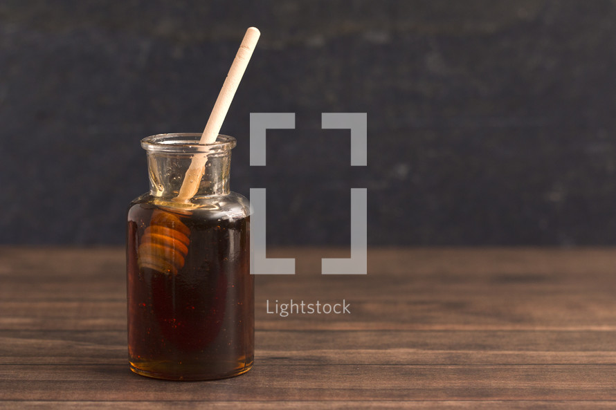 Honey with a Honeycomb Spoon on a Wood Background