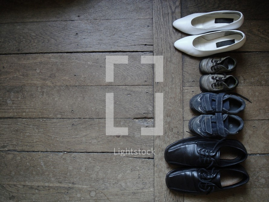 Family's shoes lined up on a wood floor.  children, kid, kids, together, joy, parenting, parents, child, baby, little, big, shoe