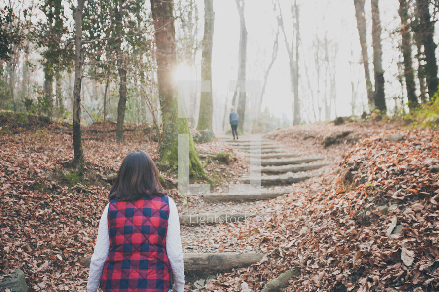 woman walking up steps on a nature trail