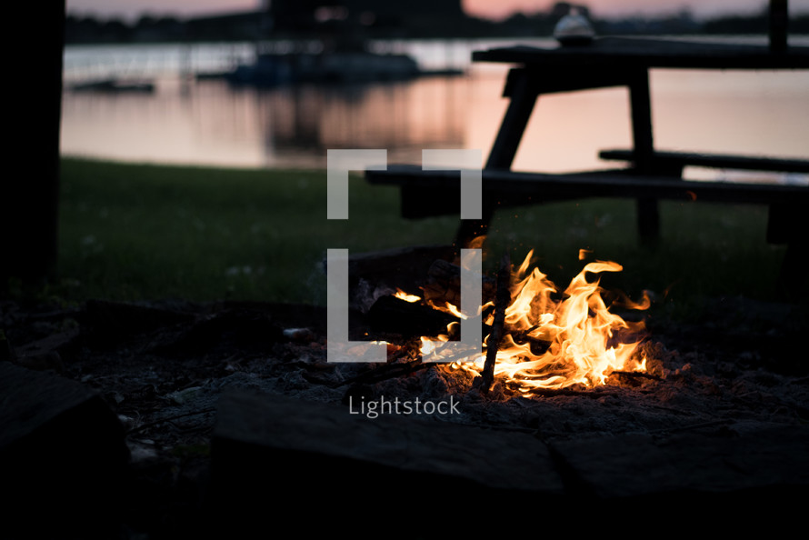 flames from a campfire by a lake