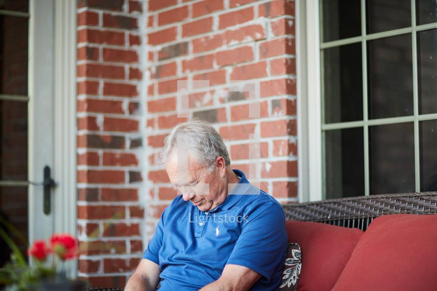 a man sitting on a porch praying