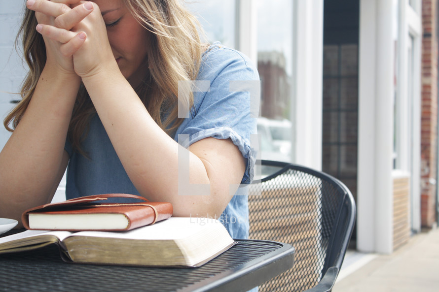 a woman sitting at an outdoor table praying with a coffee cup, Bible, and journal
